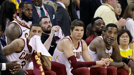 Cleveland Cavaliers' LeBron James, top left, sits on