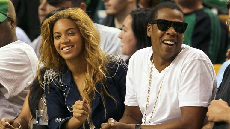 Singers Beyonce and Jay-Z sit courtside during a