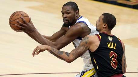 Warriors forward Kevin Durant is defended by Cavaliers