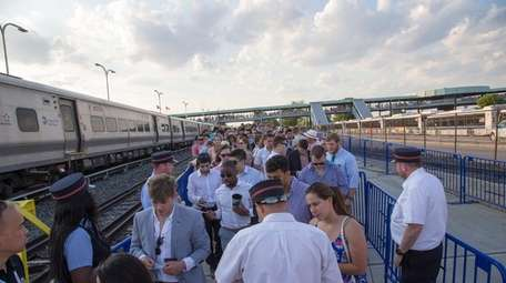 Race fans crowd the LIRR station as they