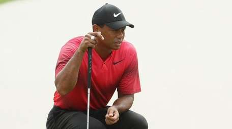 Tiger Woods lines up a putt during the