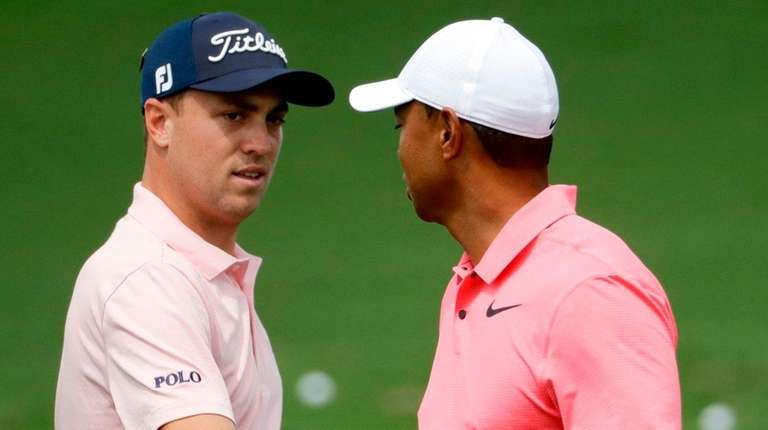 Tiger Woods, right, greets Justin Thomas on the