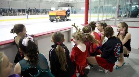 Young figure skaters wait for the ice to