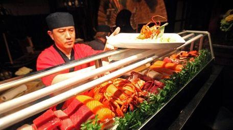 A sushi chef prepares orders at Burton &