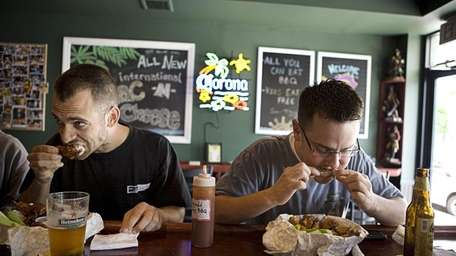 Bryan Accettella, 28, right, chows down on some