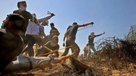 Palestinian protesters use slingshots to hurl stones toward