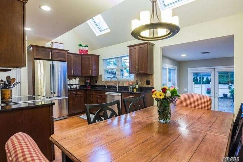 The updated eat-in kitchen features vaulted ceilings with