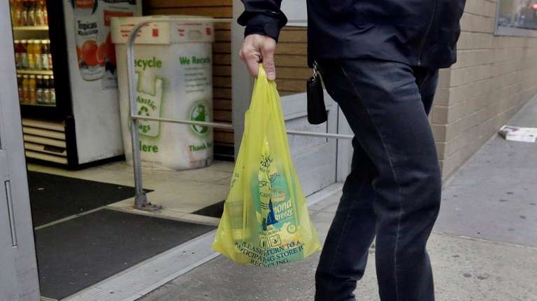 A man carries his purchase in a plastic