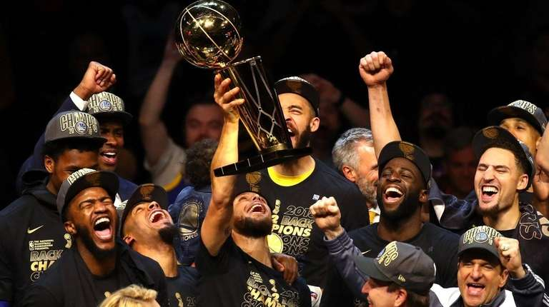 Stephen Curry (with trophy) and the Warriors