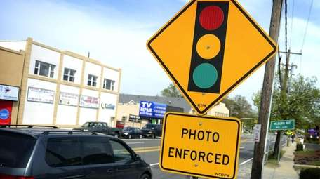 A red-light traffic camera sign at the intersection