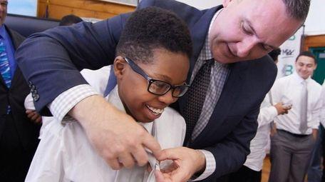 Allan Belizarre, 14, of Brentwood, gets his tie