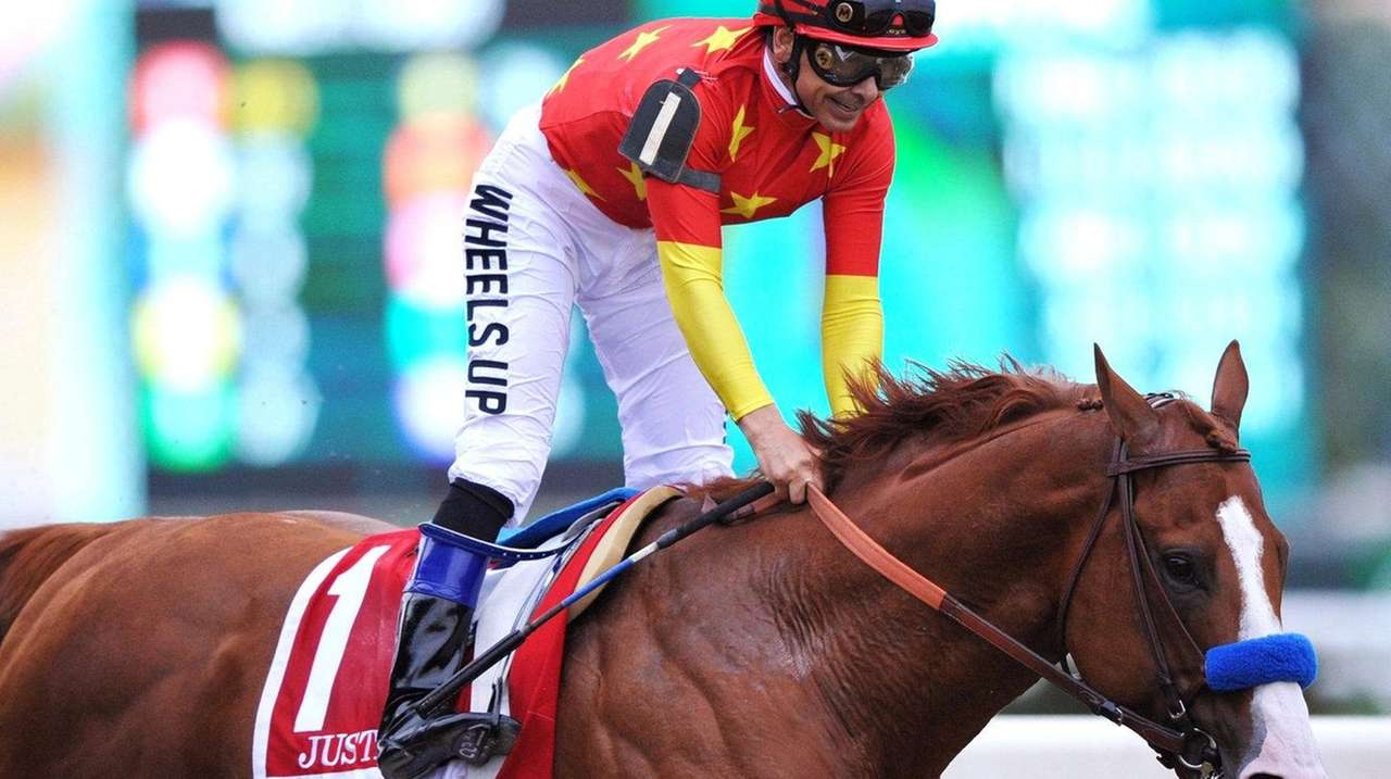 Justify, ridden by jockey Mike Smith, crosses the