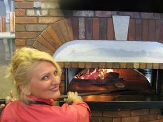 Patrizia Colatosi takes bread out of the wood-burning