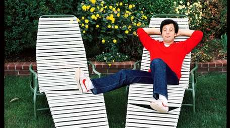 Billy Joel rests on a chaise longue in
