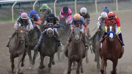 Justify with jockey Mike Smith (right) leads the