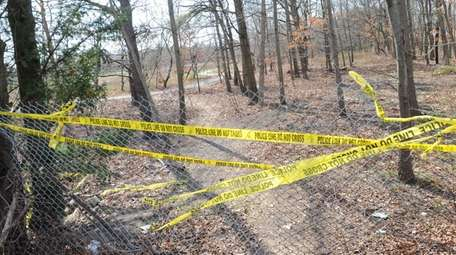 A fenced-in opening and crime tape on April