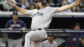 Boston Red Sox Kevin Youkilis goes airborne to