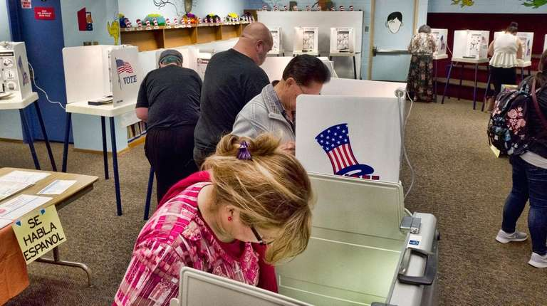Voters mark ballots at a polling place at