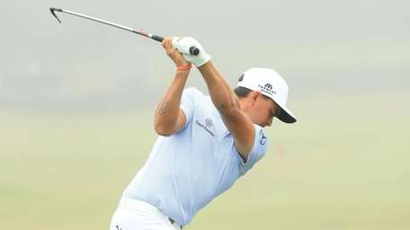 Rickie Fowler hits on the range during a