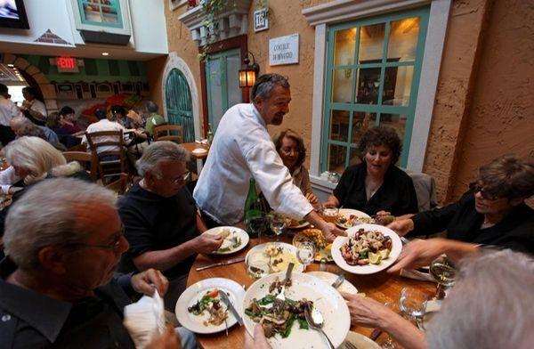 Angelo Giannuzzi, center, part-owner of the establishment, serves