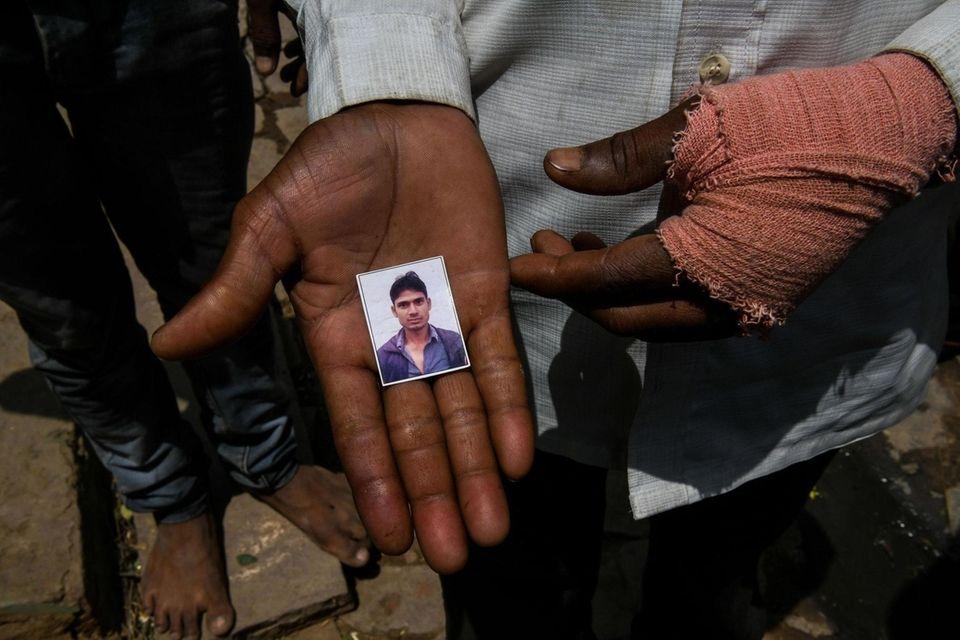 A man shows a photo of Gautam Singh,