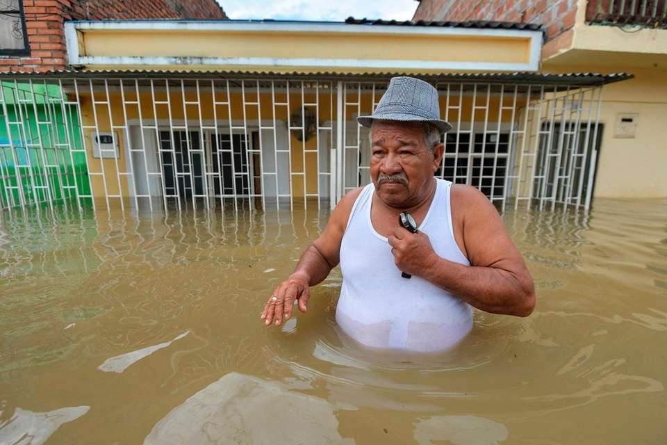 A man wades along a flooded street in