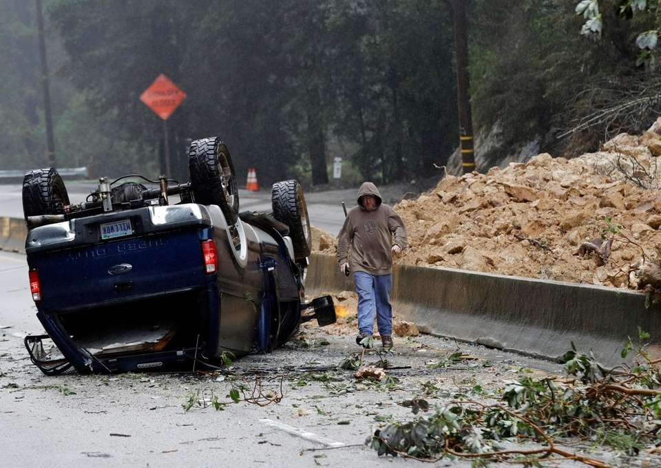 A tow truck operator walks past an overturned