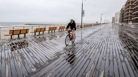 A lone biker rides along the boardwalk on