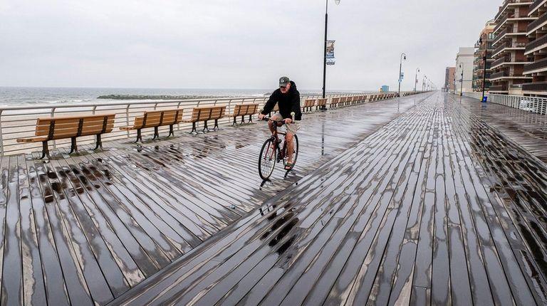 A lone biker rides along the boardwalk on