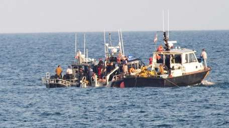 Police and recovery boats gather around a buoy