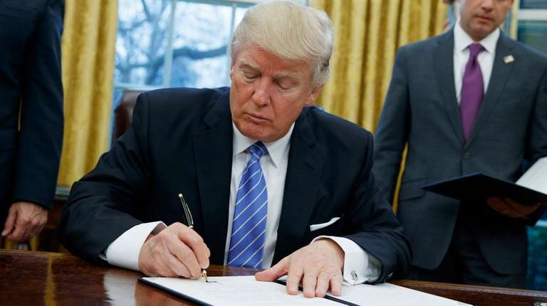 President Donald Trump signs an executive order in