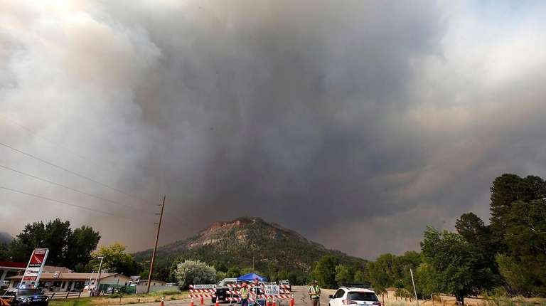 Smoke rises from behind the U.S. Highway 550
