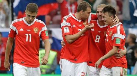 Russia players celebrate after scoring during a Group