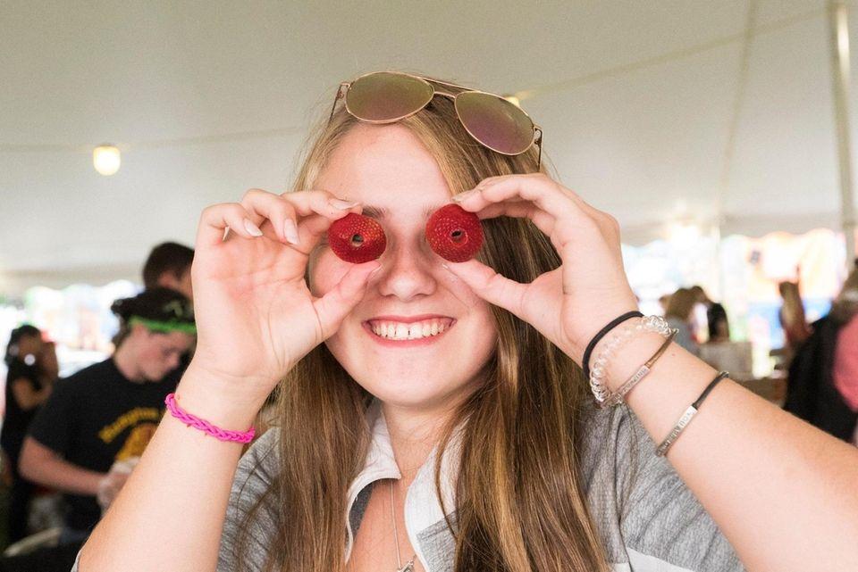 Courtney Kruk, 17, of Southold hulls strawberries at