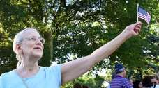 Pamela Swanson of Cold Spring Harbor waves a