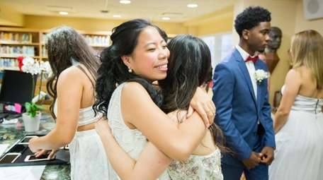 Chloe Chun of Great Neck, 17, left, embraces