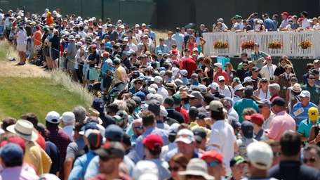 Early crowds gather on the first fairway at