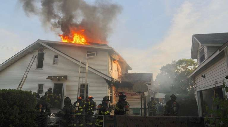 Firefighters from several departments battle a house fire
