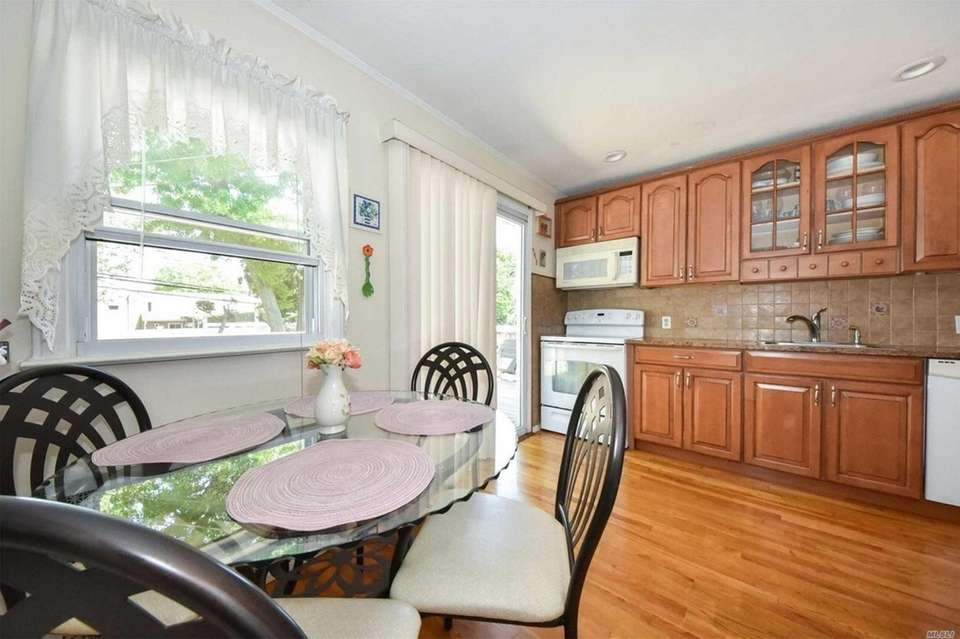 The eat-in kitchen features wood floors, granite counters