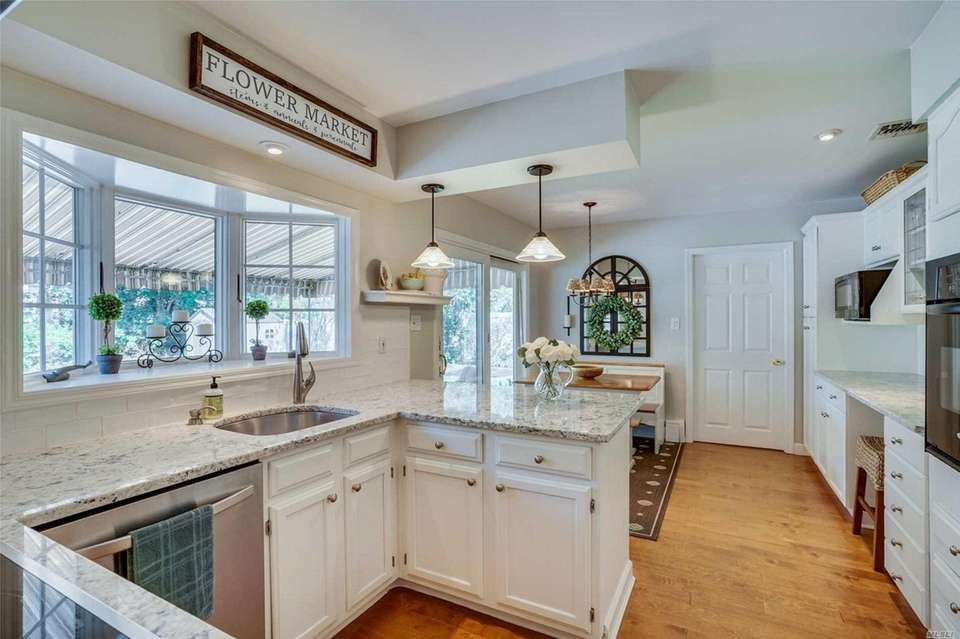 The expanded eat-in kitchen features granite countertops, white