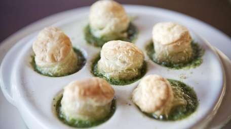 Escargots are served topped with a puff pastry