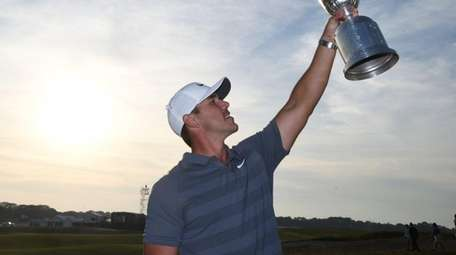 Brooks Koepka lifts the trophy after winning the