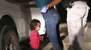 A 2-year-old Honduran asylum seeker cries as her