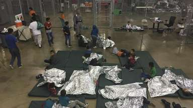 Children are held by U.S. Border Patrol agents