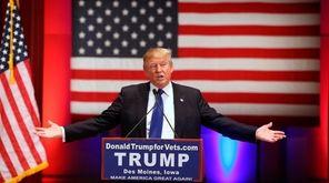 Donald Trump speaks behind a DonaldTrumpforVets.com sign at