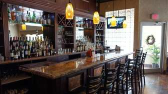 The bar at Piccolo Mondo features dark wood