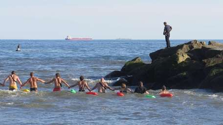 Rescue personnel form a human chain as they