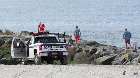 Long Beach lifeguards walk along the jetties during