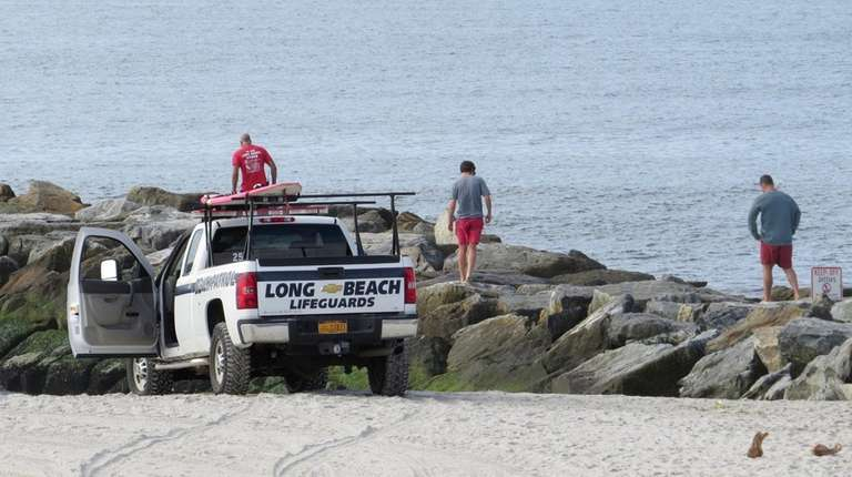 Long Beach lifeguards walk along the jetties during