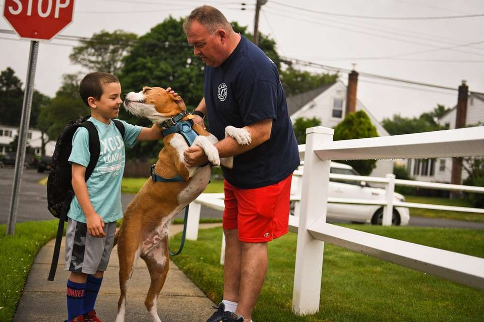 Bradyn Lewis, 7, pets his dog, Shea, while